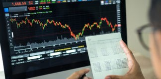 Wibest Broker- Asian Market: A hand holding a piece of paper with stocks being seen on the background.