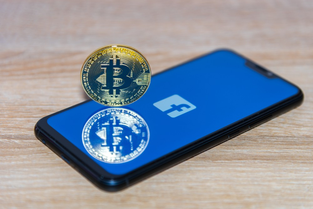 facebook logo with a bitcoin net to it on the phone