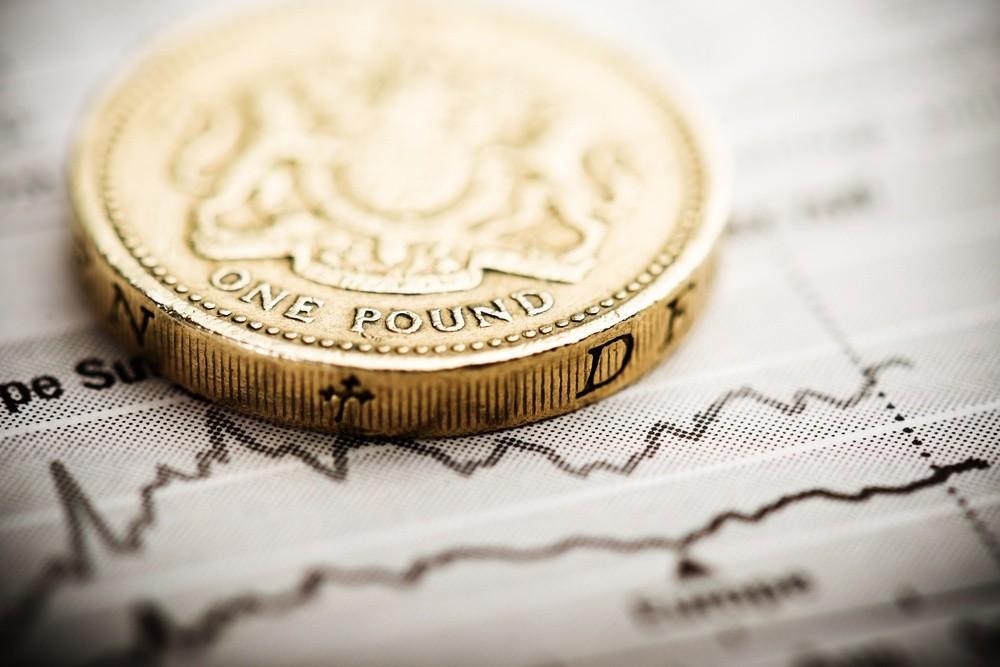 Wibest – GBPUSD: A close up of a British pound coin over a chart