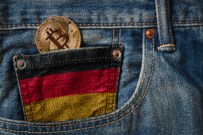 German: Golden BITCOIN (BTC) cryptocurrency in the pocket of jeans with the flag of Germany