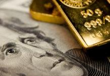 Wibest – Spot gold prices: A close up shot of a gold bar over a US dollar bill.