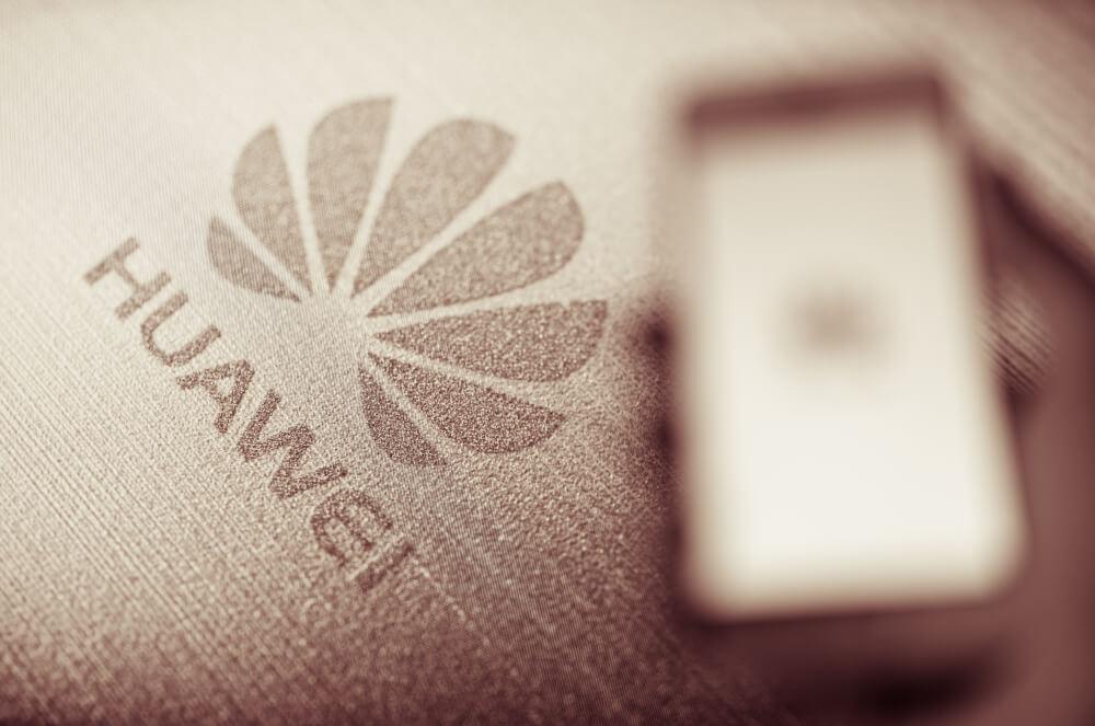 Huawei: Blurred hand holding smartphone with billboard of huawei logo.