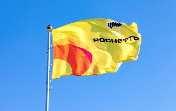 Rosneft: The flag of oil company Rosneft against blue sky.