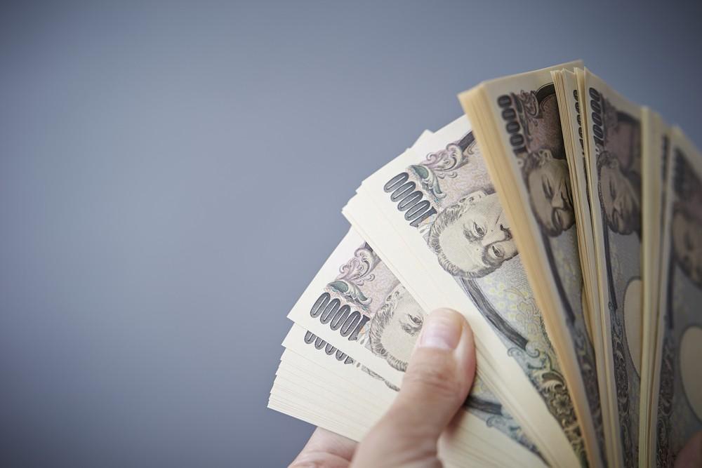 Wibest – Japan Yen: Hands holding Japanese yen bills.