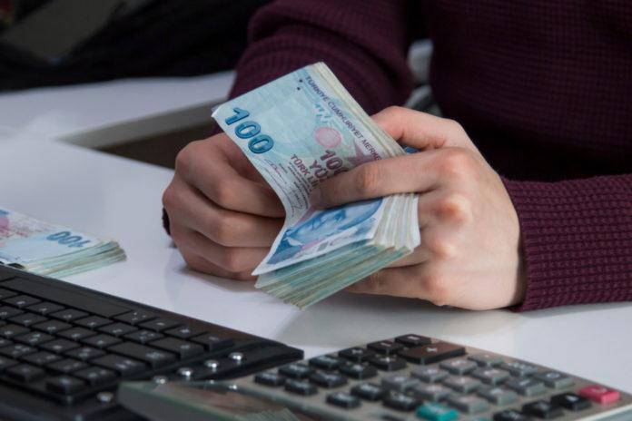 Wibest – Turkish: Hands holding Turkish lira bills in front of a keyboard.