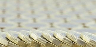 Wibest – USD GBP: British pound coins arranged in a row.