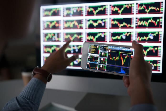 Trader: Hands of trader holding smartphone with stock market app