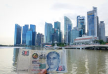 Wibest – Monetary Authority of Singapore: Singaporean dollar in held by a man and a city in the background.