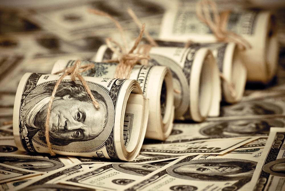 Wibest – US Federal Reserve: US dollar bills rolled up.