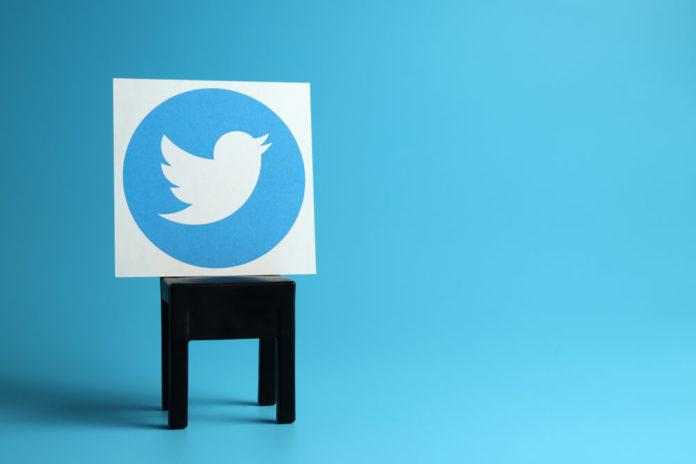 Twitter: Twitter logo on a black chair, light blue background.