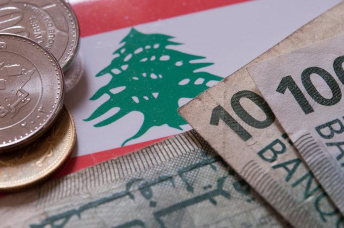 Wibest – Lebanese: The Lebanese pound coins and bills over Lebanon's flag.