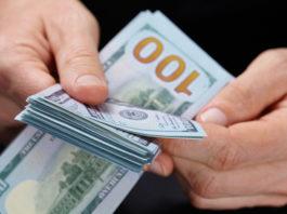 Wibest – USA Jobs: A man counting US dollar bills.