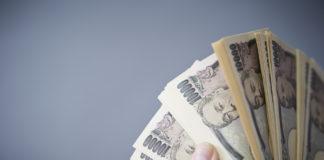 Wibest – Yen exchange rate: Hands holding Japanese yen bills.