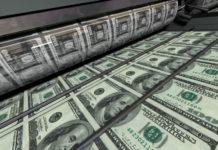 The Greenback: Concept Printing Money 100 Dollar Bills closeup.