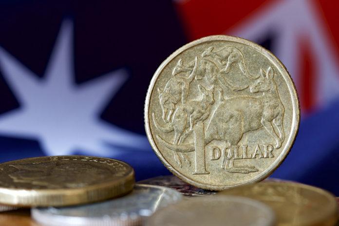 Wibest – Australian Money: Australian dollar coins and the Australian flag behind.
