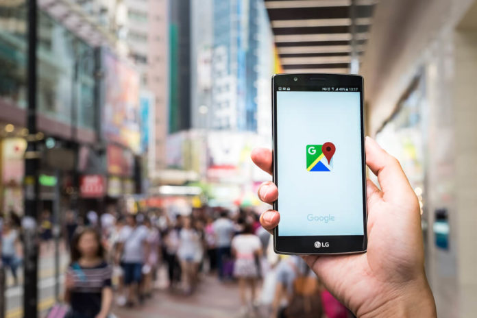 A man hand holding screen shot of google maps app showing on LG G4.