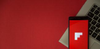 Flipboard logo on smartphone screen placed on laptop keyboard.